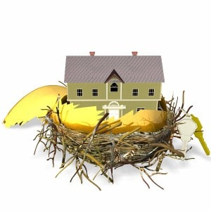 large golden hatched egg sitting in a nest with a brand new house and set of keys