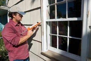 A Man Caulking An Outside Window To Insulate Against the Winter Weather