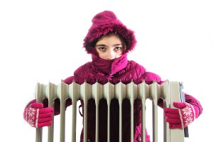 Young Girl in Warm Winter Jacket with Hood Near a Heater.